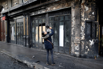 A person makes a picture outside a vandalized restaurant the morning after clashes with protesters wearing yellow vests, a symbol of a French drivers' protest against higher diesel taxes, in Paris