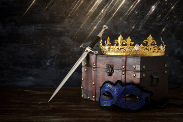 low key image of beautiful queen/king crown, mysterious mask and sword. fantasy medieval period.