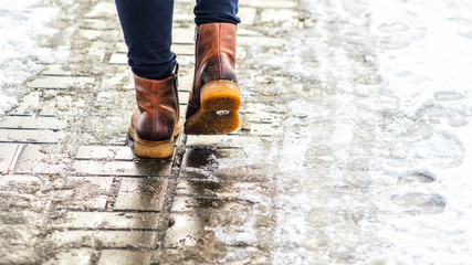 Walk on wet melted ice pavement. Back view on the feet of a man walking along the icy pavement. Pair of shoe on icy road in winter. Abstract empty blank winter weather background