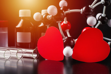 Two red paper hearts and molecular structure model on a black background. Love chemistry concept