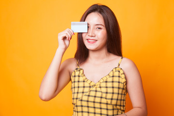 Young Asian woman with  blank card over her eye.