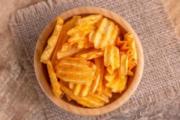 Crispy corrugated potato chips in wooden bowl on burlap napkin