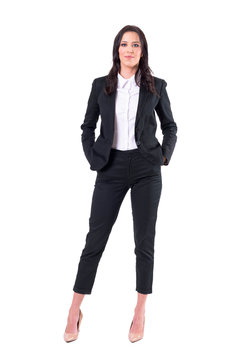 Happy relaxed confident successful business woman with hands in pockets looking at camera. Full body isolated on white background.
