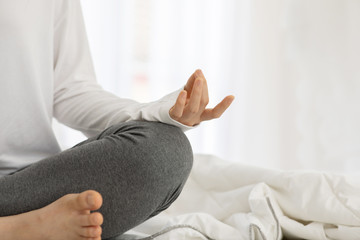Close up hands of woman doing yoga lotus pose on bed in the bedroom after wake up in the  morning to meditation and relax balance for good health,Warm tone,Healthy Concept