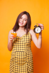 Asian woman with a clock drink orange juice.