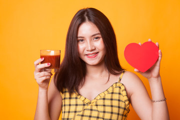 Young Asian woman with tomato juice and red heart.