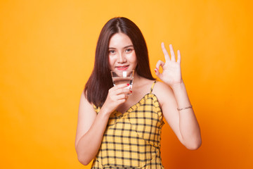 Young Asian woman show OK with a glass of drinking water.