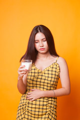Asian woman drinking a glass of milk got stomachache.