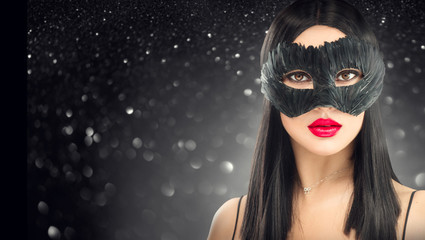 Wall Mural - Beauty glamour brunette woman wearing carnival dark mask, party over holiday glowing black background