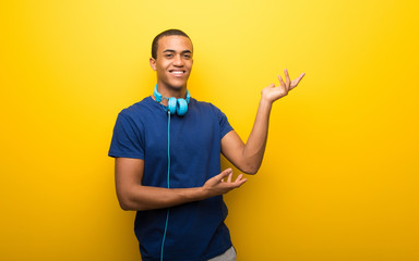African american man with blue t-shirt on yellow background extending hands to the side for inviting to come
