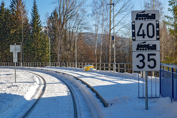 The snowy railway station in the mountains. The empty platform in the winter nature. Harrachov, Mountains Krkonose, Czech Republic.