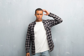 Young african american man with checkered shirt having doubts while scratching head