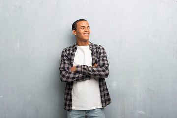 Young african american man with checkered shirt looking up while smiling