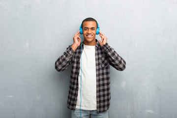 Young african american man with checkered shirt listening to music with headphones