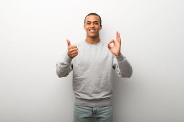 African american man on white wall background showing ok sign with and giving a thumb up gesture