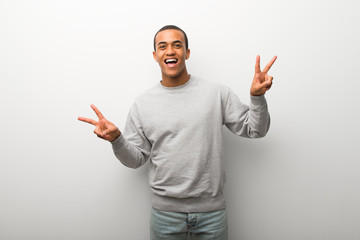 African american man on white wall background smiling and showing victory sign with both hands