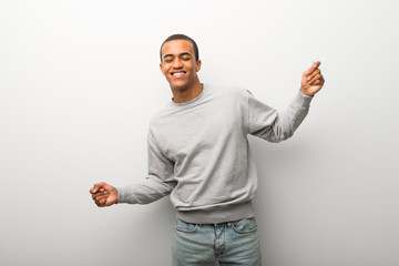 African american man on white wall background enjoy dancing while listening to music at a party