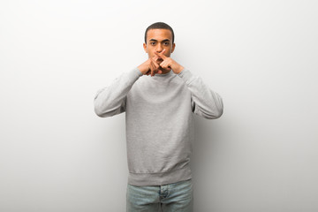 African american man on white wall background showing a sign of silence gesture