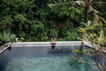 Slim brunette woman in swimsuit relaxing on edge infinity pool in jungle. Palms around and crystal clean water