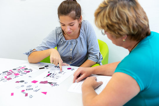 Therapist working with a teenage girl with learning difficulties to master logical tests.