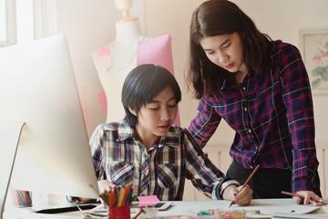 Two Asian fashion designer working in workshop