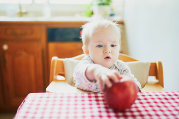 Cute baby girl eating apple in the kitchen