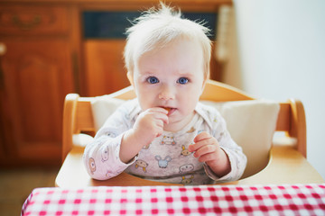 Cute baby girl feeding herself with finger food in the kitchen