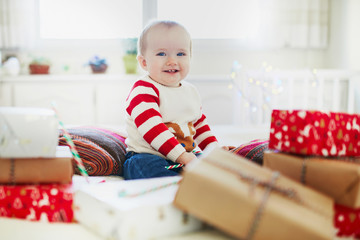 Happy little baby girl opening Christmas presents on her very first Christmas