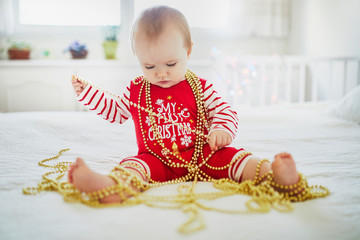 Happy little baby girl wearing pyjamas playing with New year tree decorations