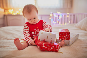 Happy little baby girl wearing pyjamas opening Christmas presents