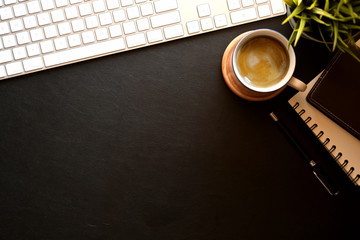 Modern dark leather office desk keyboard computer, glasses, coffee mug, house plant and copy space