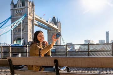 Touristin auf einer Sightseeing Tour vor der Tower Bridge in London macht ein Selfie von sich mit Ihrem Handy