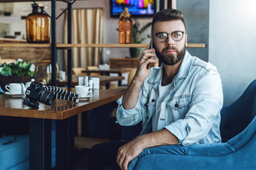 Young attractive bearded hipster man in trendy glasses sits in a cafe during lunch, talking on a cell phone. On the table is a camera with a tripod and a cup of coffee. Lifestyle, leisure, pastime.