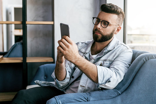 Young smiling bearded businessman is sitting in cafe, using smartphone. Freelancer work in coffee shop. Hipster man checking social media. Man learning online.Online learning, education for adilte.
