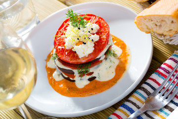 Stack of fried eggplant with tomatoes and piquant sauce