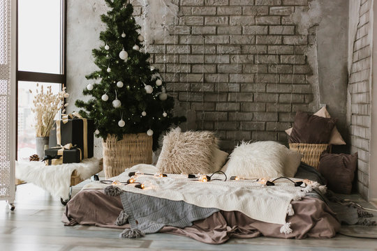 Modern living room with a bed, a Christmas tree, a window and flashlights