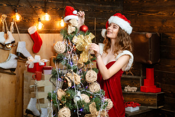 Beauty Model Girl in Santa Hat on home design decorate. Friendly and joy. Happy people. Christmas decorations and gift box on wooden background. True Emotions.