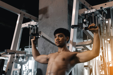 Hand man pulling bar weight at indoor gym.