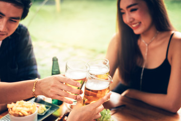 Young asian people having fun at drinking with cheering with beer at restaurant.