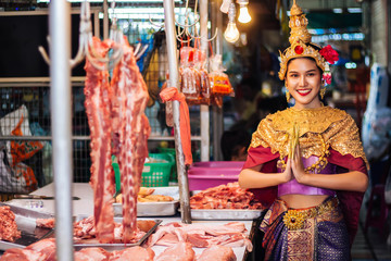 Models in Thai dance are sawasdee in market in Thailand.