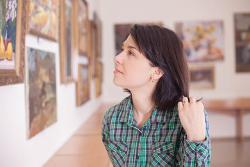A young beautiful woman looking at painting.