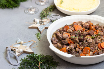 Beef bourguignon or meat stew with vegetables and herbs in a casserole.