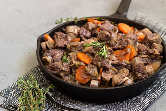 A skillet with beef bourguignon or meat stewed with sausages, carrots, garlic, onion, red wine, fresh herbs and spices.