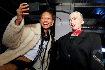 """Model Adesuwa Aighewi takes a selfie as she is interviewed by Sophia, a humanoid robot created by Hanson Robotics, backstage before the """"Alexander Wang Collection 2"""" presentation in Brooklyn, New York City"""