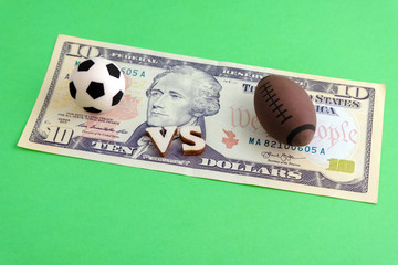 Classic soccer vs American football or rugby. Concept sport and money. Ten dollars and souvenir balls on a green background. Sports betting.