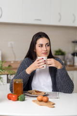 Pensive woman sitting at dining table and enjoying in cup of coffee after breakfast