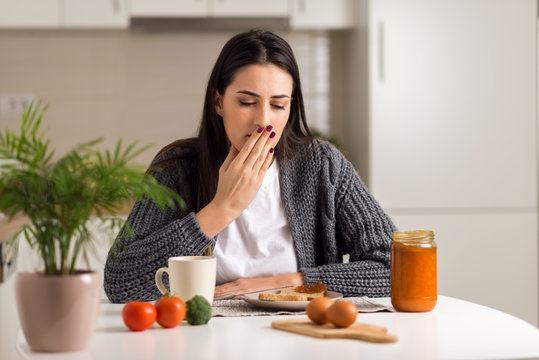 Young  woman feeling nausea during breakfast time