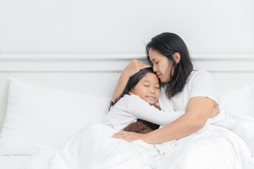 Mother hugging and kiss her daughter on bed