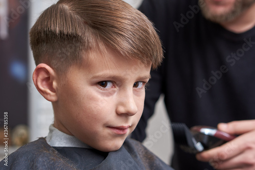European Boy Looking Into A Camera While Getting Haircut In