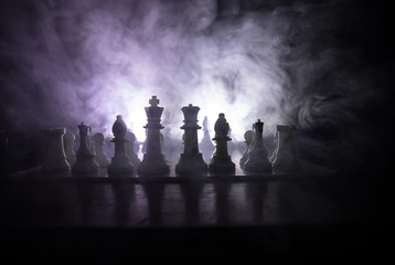 Chess board game concept of business ideas and competition or strategy ideas concept. Chess figures on a dark toned foggy background.